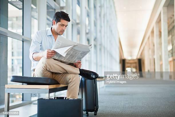 Businessman reading newspaper on bench