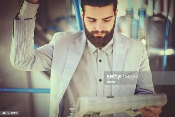 Geschäftsmann liest Zeitung auf die Fahrt.