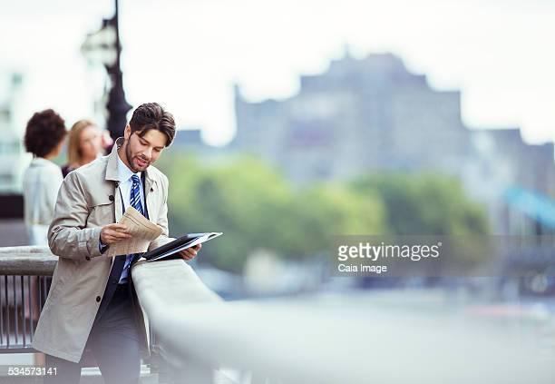 Businessman reading newspaper on urban waterfront