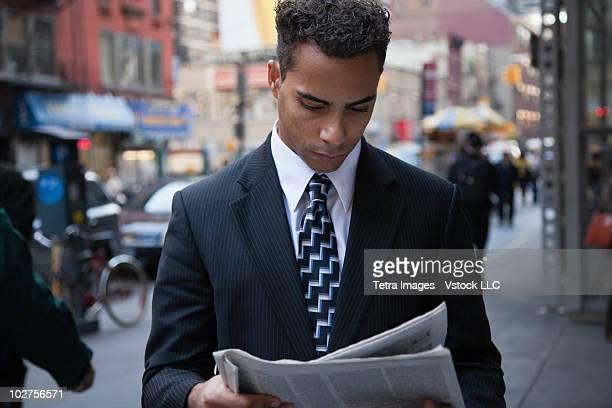 Businessman reading newspaper while walking down street