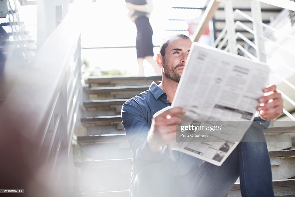 Businessman reading newspapers on staircase : Stock Photo