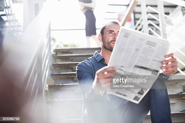 Businessman reading newspapers on staircase