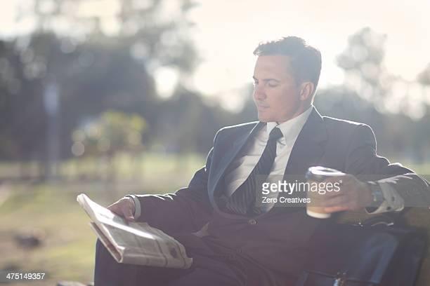 Businessman reading on park bench