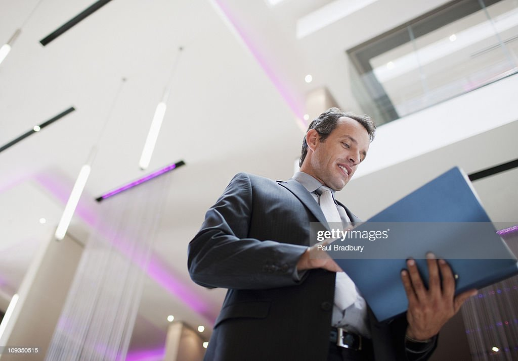 Businessman reading report in lobby : Stock Photo