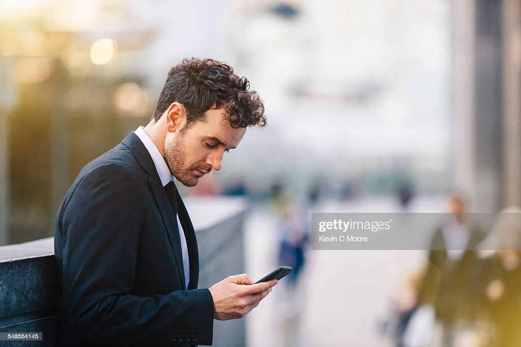 Businessman reading smartphone texts on city street
