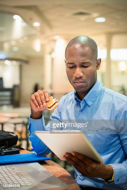 Businessman reading tablet during lunch in food court