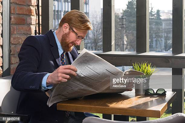 Businessman reading the newspaper on a sunlit terrace