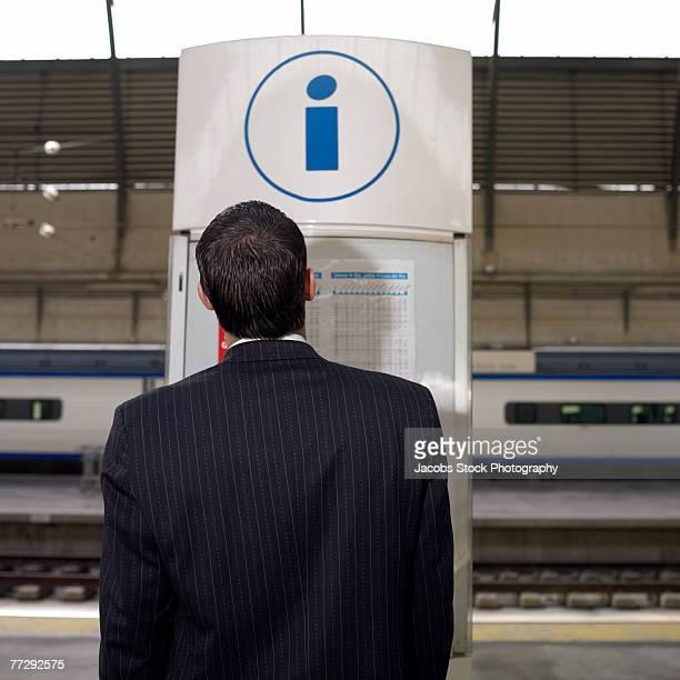 Businessman reading train schedule on information kiosk