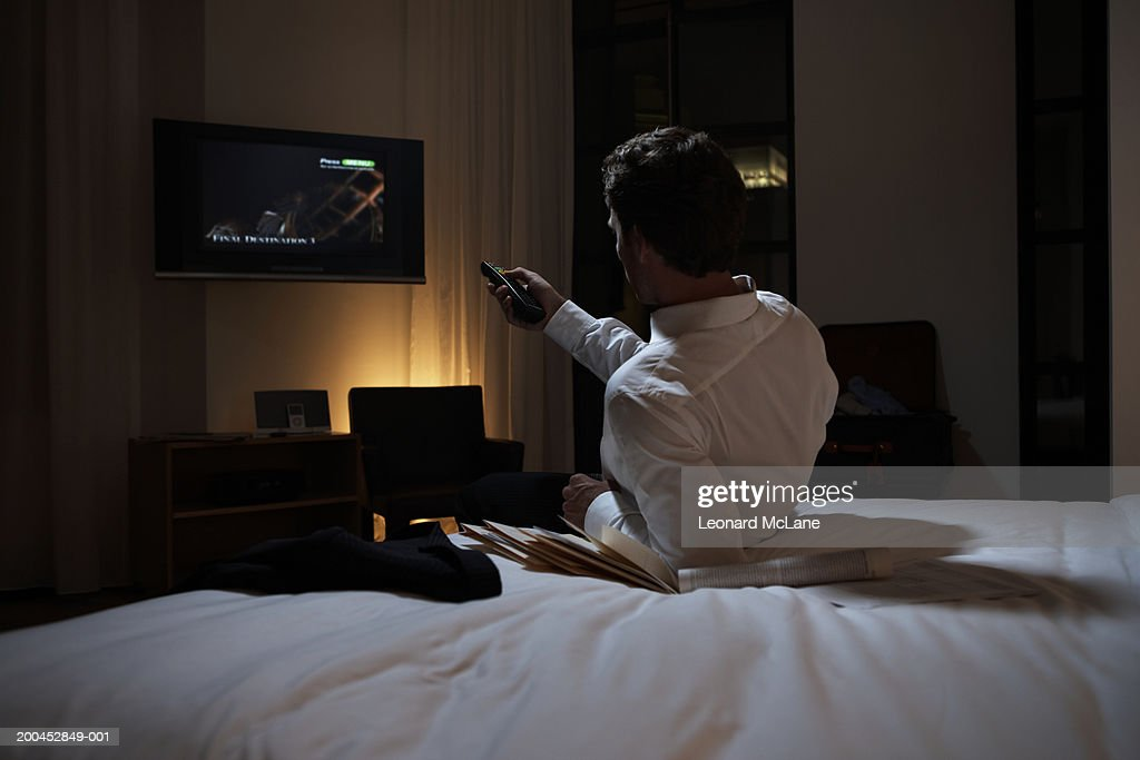 Businessman reclining on bed using remote control, rear view : Stock Photo