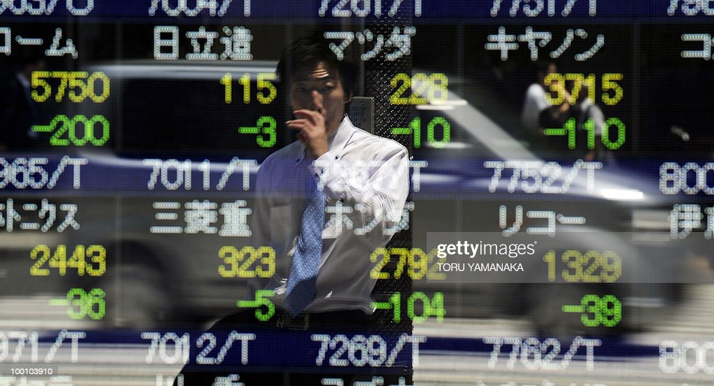 A businessman reflects on an electric quotation board flashing share prices of the Tokyo Stock Exchange (TSE) in front of a securities company in Tokyo on May 21, 2010. Japanese shares plunged 2.51 percent by noon following Wall Street's biggest drop in more than a year and as the continued strength of the yen prompted investors to sell shares. AFP PHOTO/Toru YAMANAKA