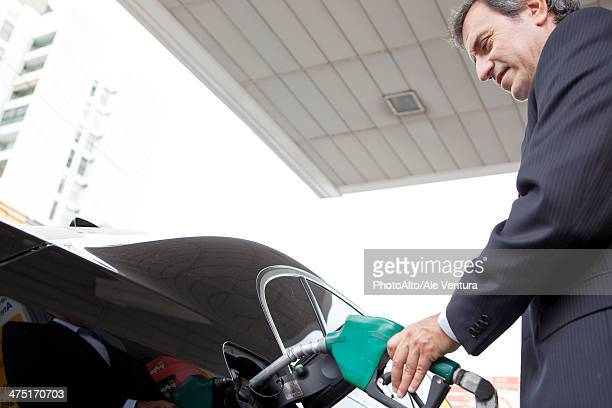 Businessman refueling car at gas station