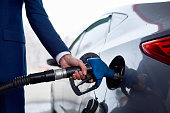 Side view closeup of unrecognizable businessman refueling gas tank iof luxury car in modern petrol station