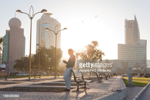 Businessman relaxes against bench, checks text : Stock Photo