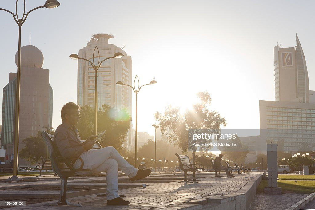 Businessman relaxes on bench, uses digital tablet : Stock Photo