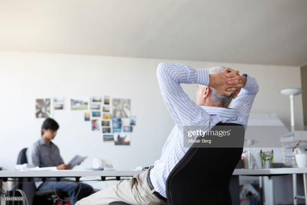 Businessman relaxing at his desk : Stock Photo