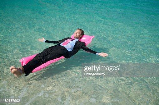 ビジネスマンリラックスに浮かぶゴムボートピンクのプール
