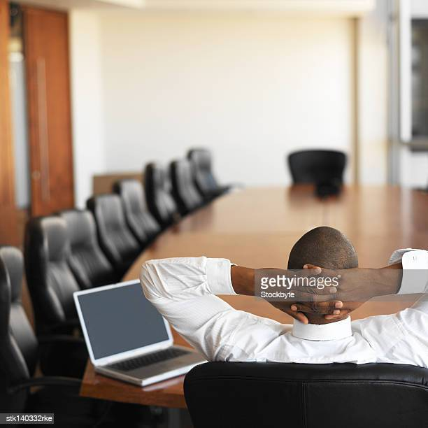 businessman relaxing in an empty conference room with a laptop in front of him