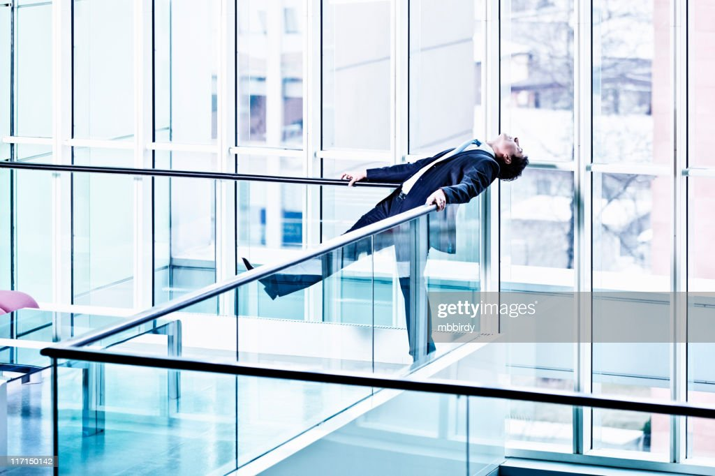 Businessman relaxing leaned on glass fence : Stock Photo