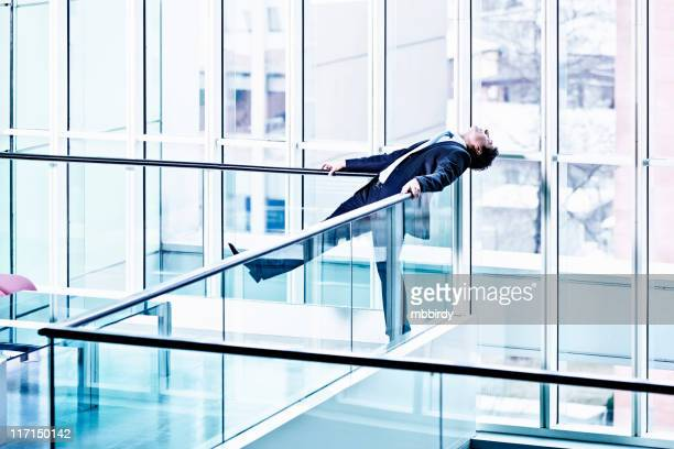 Businessman relaxing leaned on glass fence