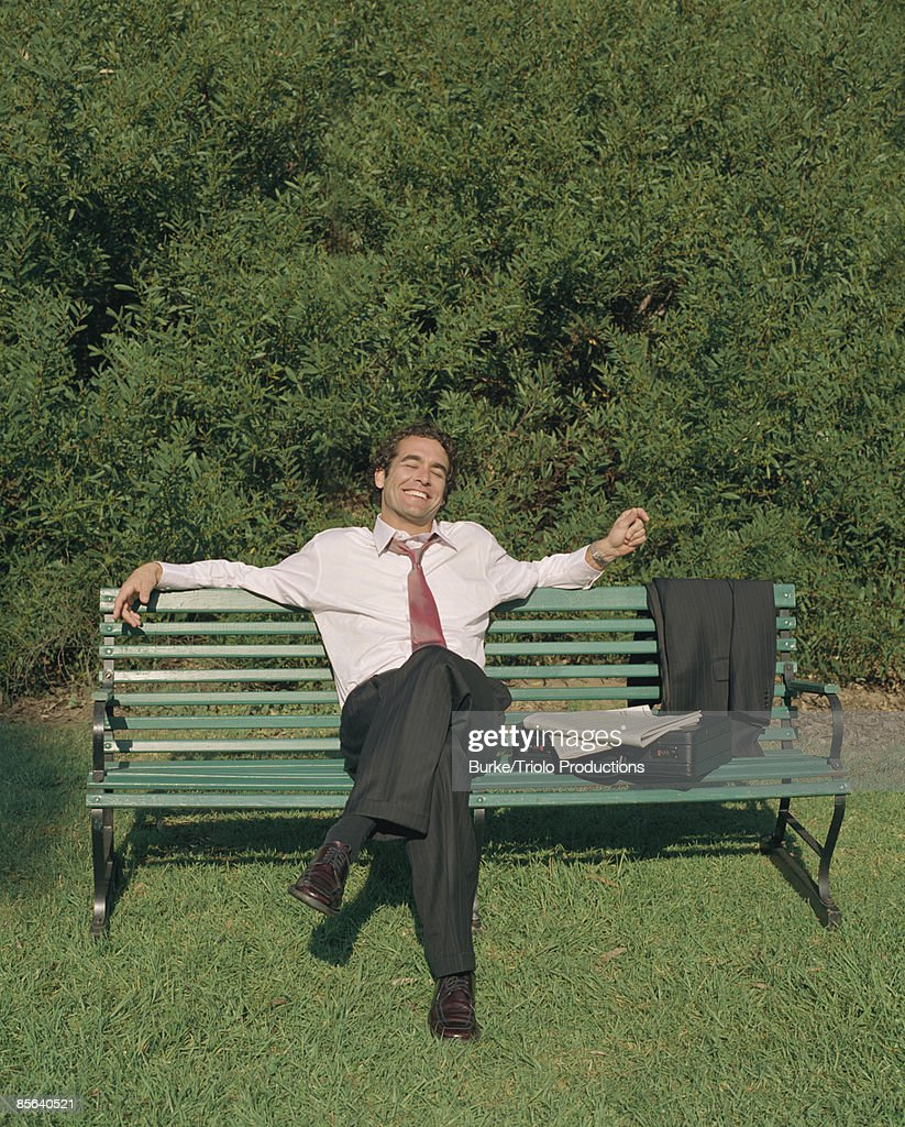 Businessman relaxing on bench : Stock Photo