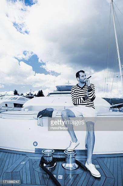 Geschäftsmann entspannenden an Bord der Jacht. Rauchen Zigarre.