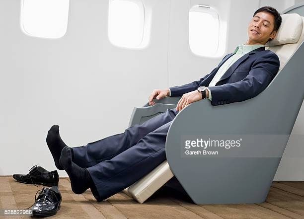 Businessman relaxing on reclining chair on airplane