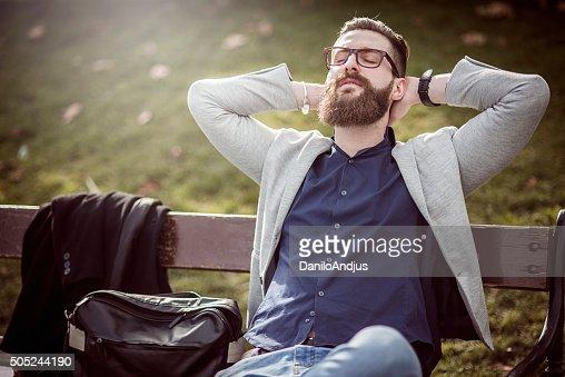 Uomo d'affari rilassante sulla panchina dopo il lavoro