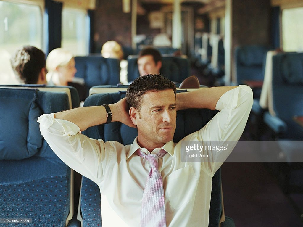 Businessman relaxing on train, hands behind head (focus on man)