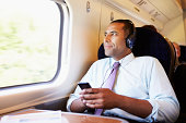 Businessman Relaxing On Train Listening To Music with headphones on