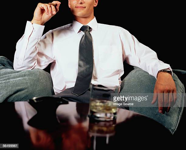 Businessman relaxing with a drink and a cigar