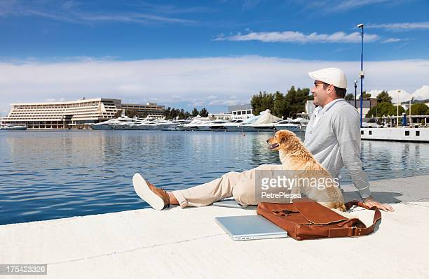 Businessman relaxing with his dog in the Yacht Harbor.