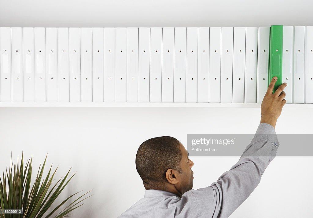 Businessman removing binder from shelf