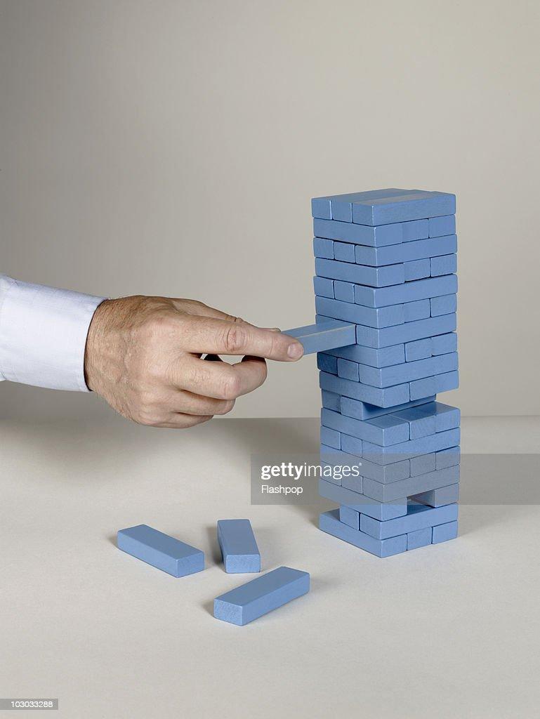 Businessman removing building block : Stock Photo