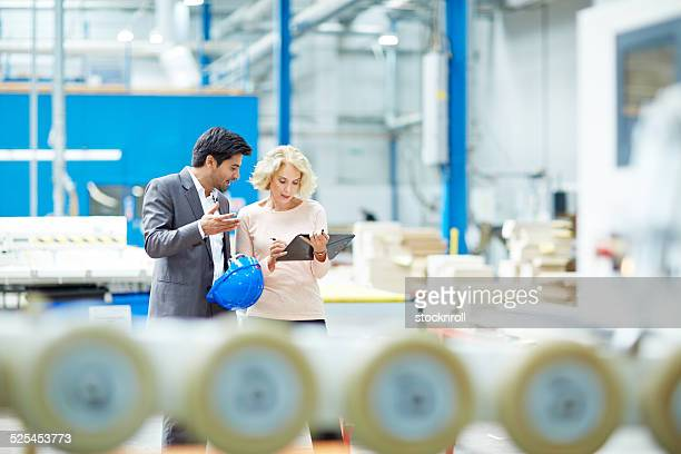 Businessman reporting production details to senior manager