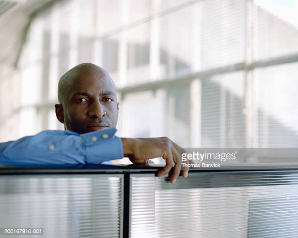 Businessman resting arm on cubicle wall, portrait