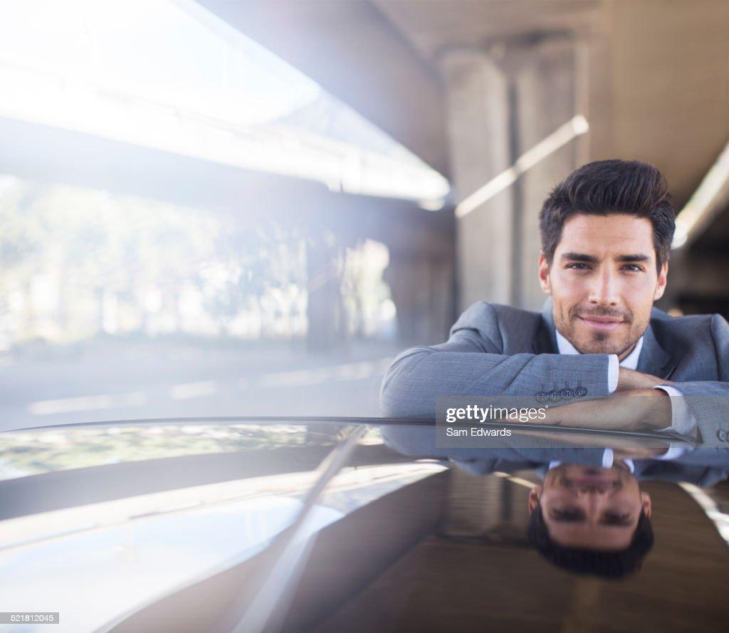 Businessman resting on car in parking garage
