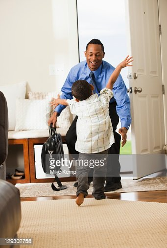 Businessman returning from work being greeted by son : Stock Photo