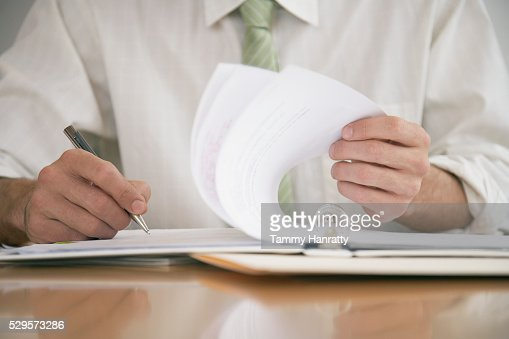 Businessman reviewing paperwork : Stock-Foto