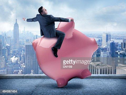 Businessman Riding A Piggy Bank In Urban Scene