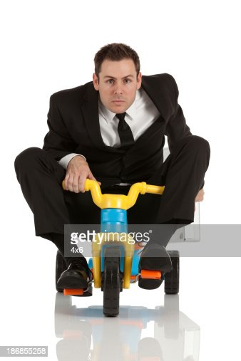 Businessman riding a tricycle