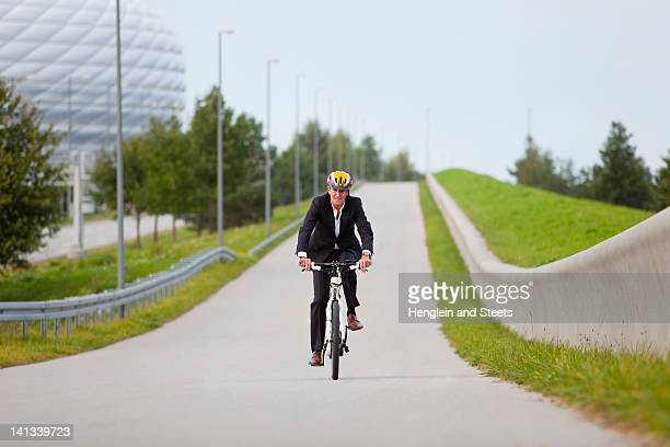 Businessman riding bicycle in urban park
