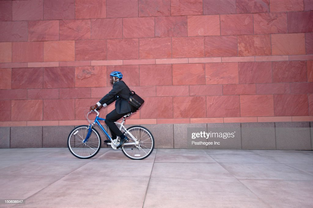 Businessman riding bicycle on sidewalk
