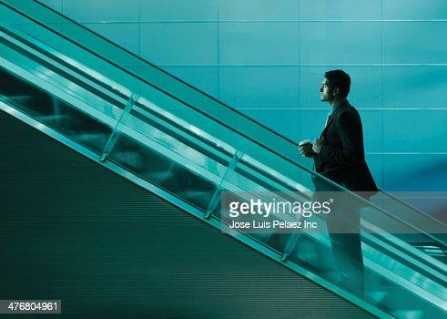 Businessman riding escalator