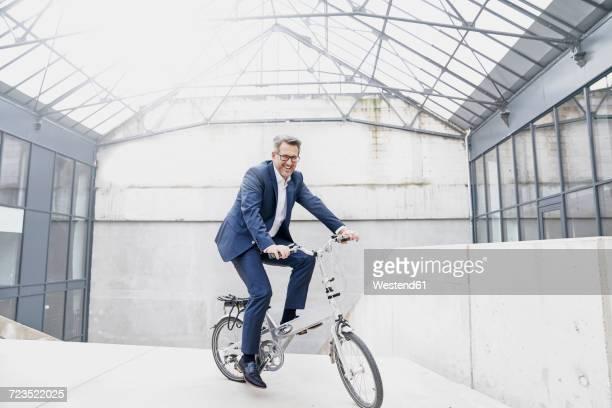 Businessman riding folding bicycle