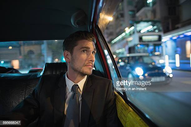 Businessman riding in back seat of car, Hong Kong.