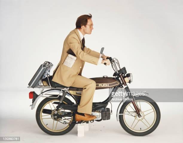 Businessman riding motorbike on white background