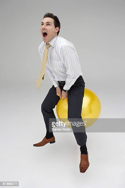 Businessman riding on a space hopper, screaming