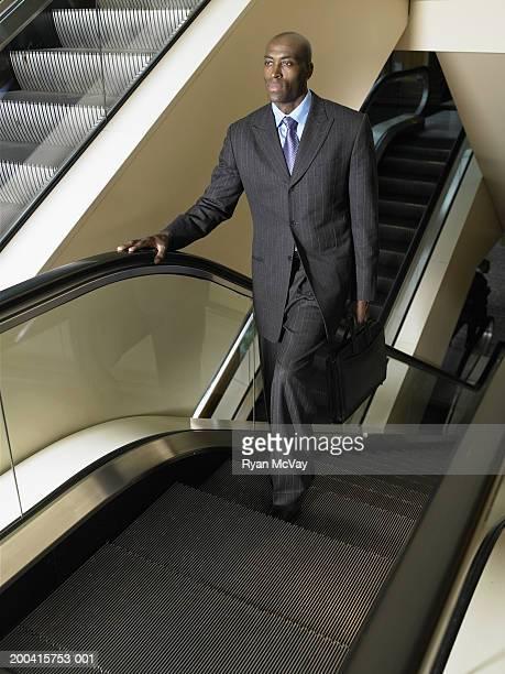 Geschäftsmann Reiten auf Rolltreppe