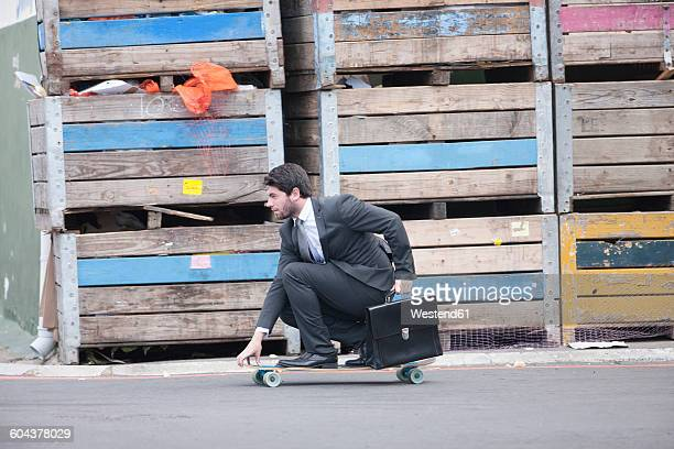 Businessman riding on skateboard
