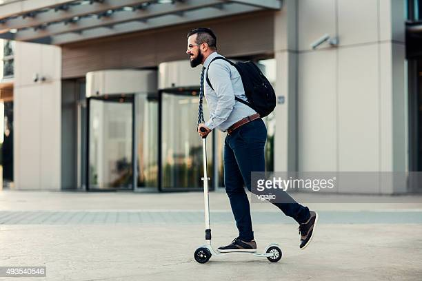 Businessman Riding Push Scooter.
